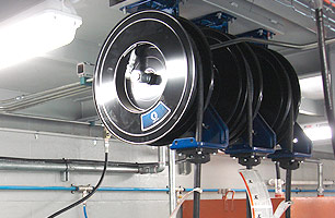 Lubrication hose reels mounted to roof of suspended ceiling workshop pit